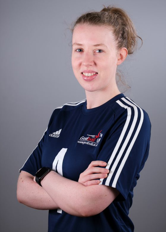 Image shows Georgie Bullen stood smiling at the camera with her arms crossed. She is wearing her GB womens kit