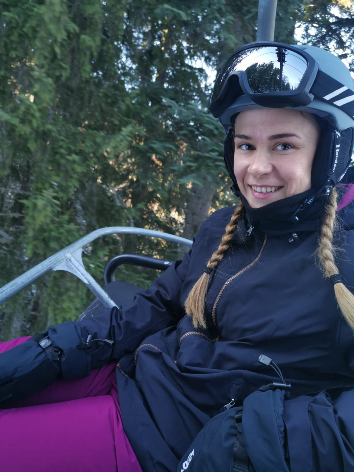 Josie Hewson pictured on a ski lift whilst wearing skiing gear including a thick black coat and purple ski trousers!