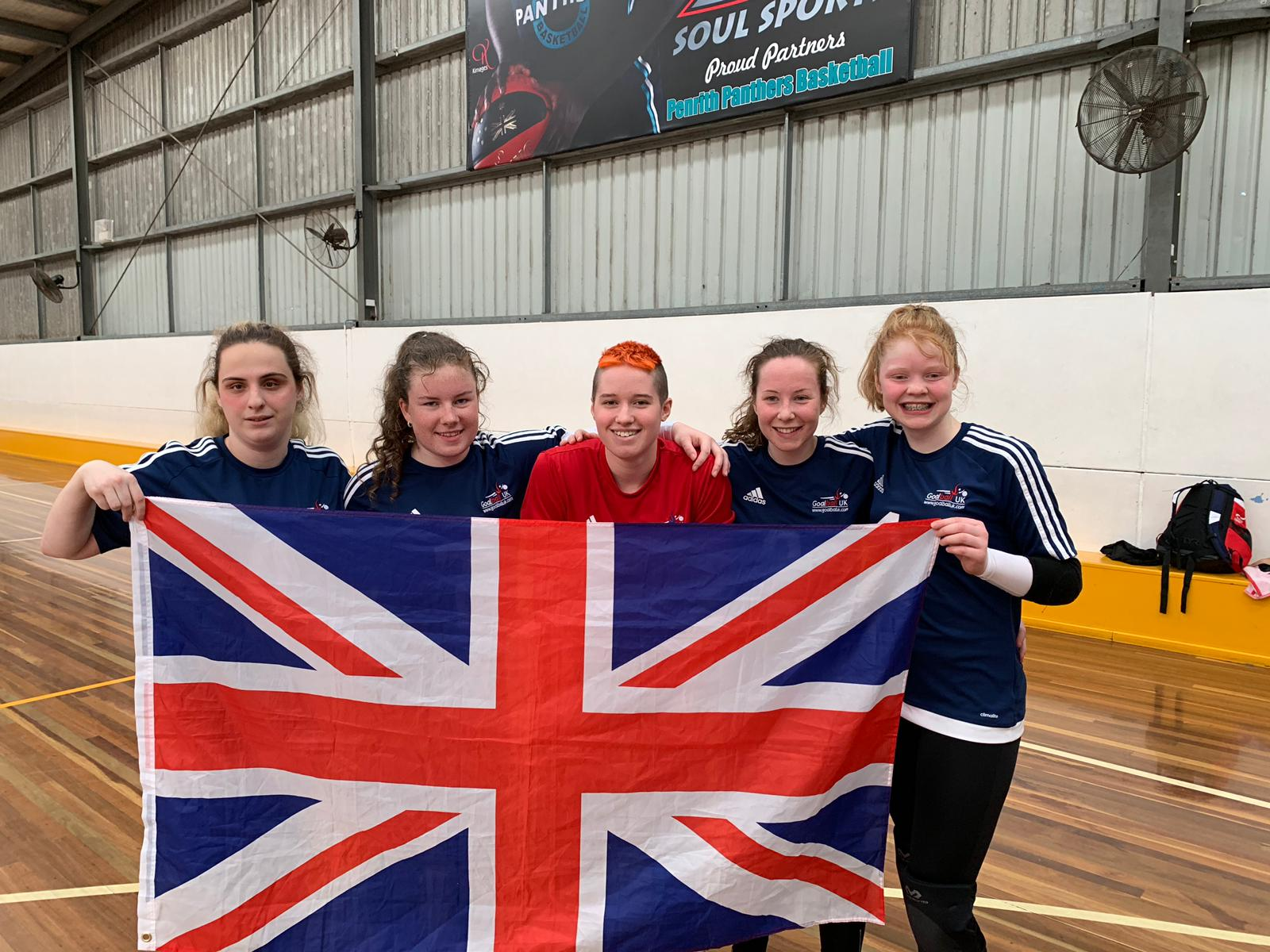 Image shows Nansi Stood with her GB under 19 teammates holding a union jack flag