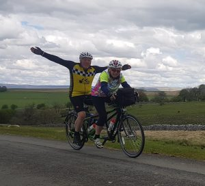 Two cyclists on a tandem, riding along a countryside road, with the stoker (at the back) with their arms outstretched
