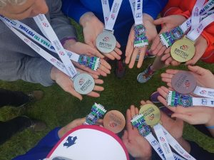A circle of 6 pairs of hands, 3 triathletes and 3 guides, holding medals (Bronze, Silver and Gold)