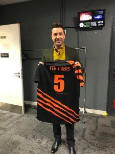 Gino D/Acampo holding a Fen Tigers shirt.