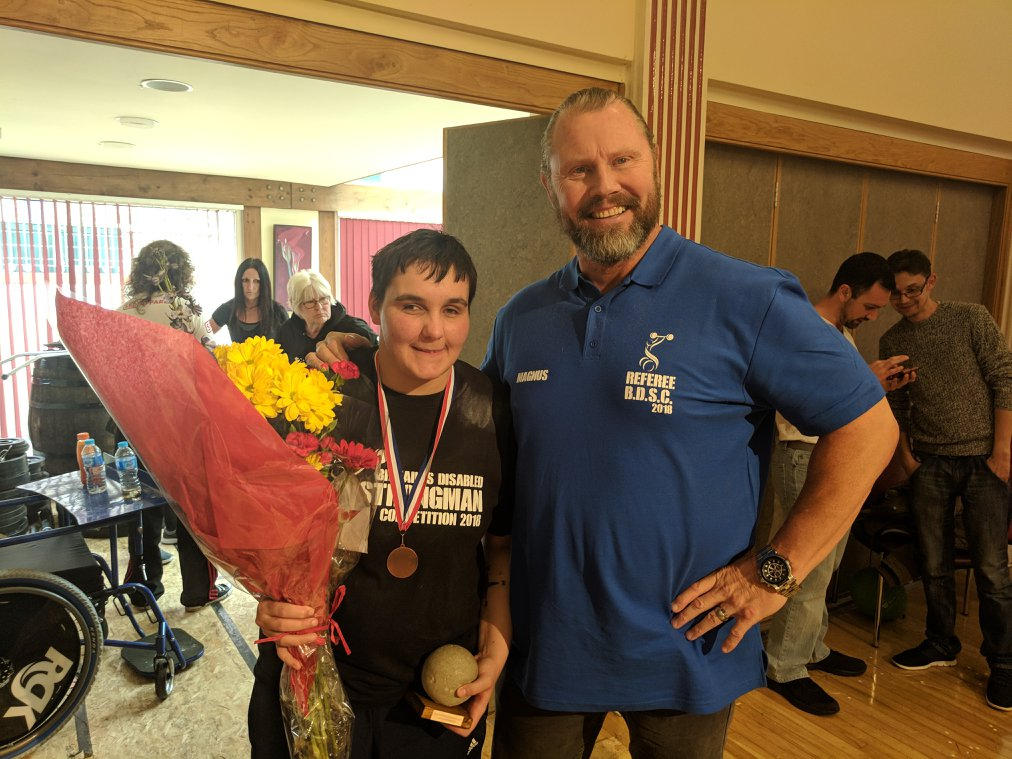 Reanne Racktoo of Blackburn Goalball Club stood with flowers and a referee after the 2018 Britains Disabled Strongman competition finishing 2nd!