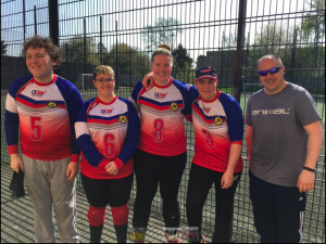 Reanne Racktoo stood in a group photo of an RNC goalball team at a tournament.
