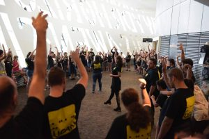 A group of UCAN members, with their hands raised, taking part in a workshop