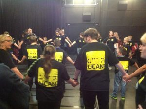A group of UCAN members stood in circles, holding hands