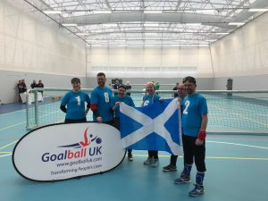 Lorna Morisset stood within a team photo of Glasgow goalball club who are holding a Scotland flag next to a Goalball UK banner.