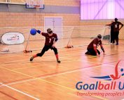 Peter Doyle shooting a goalball at an elite tournament in Longbridge, Birmingham with Matt Loftus in centre and Caleb Nanevie on the left wing.