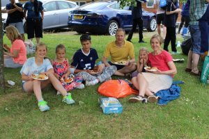 Arthur Milles with his family sat on a patch of grass at a Winchester Goalball Club social event.