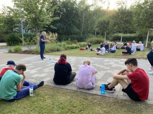Joint camp quiz picture of both groups sat on grass patches either side of a path. Kathryn is revealing the answers to the previous round!