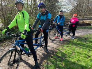 Tandem trekkers session with two duos parked up smiling to the camera in a scenic park featuring Chris Fenton.