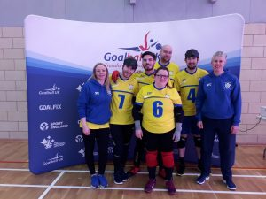 West Yorkshire team photo at the 2020 Intermediate Finals. The team are wearing their yellow 'home' kit with coaches Kelly and Kathryn either side of the team.