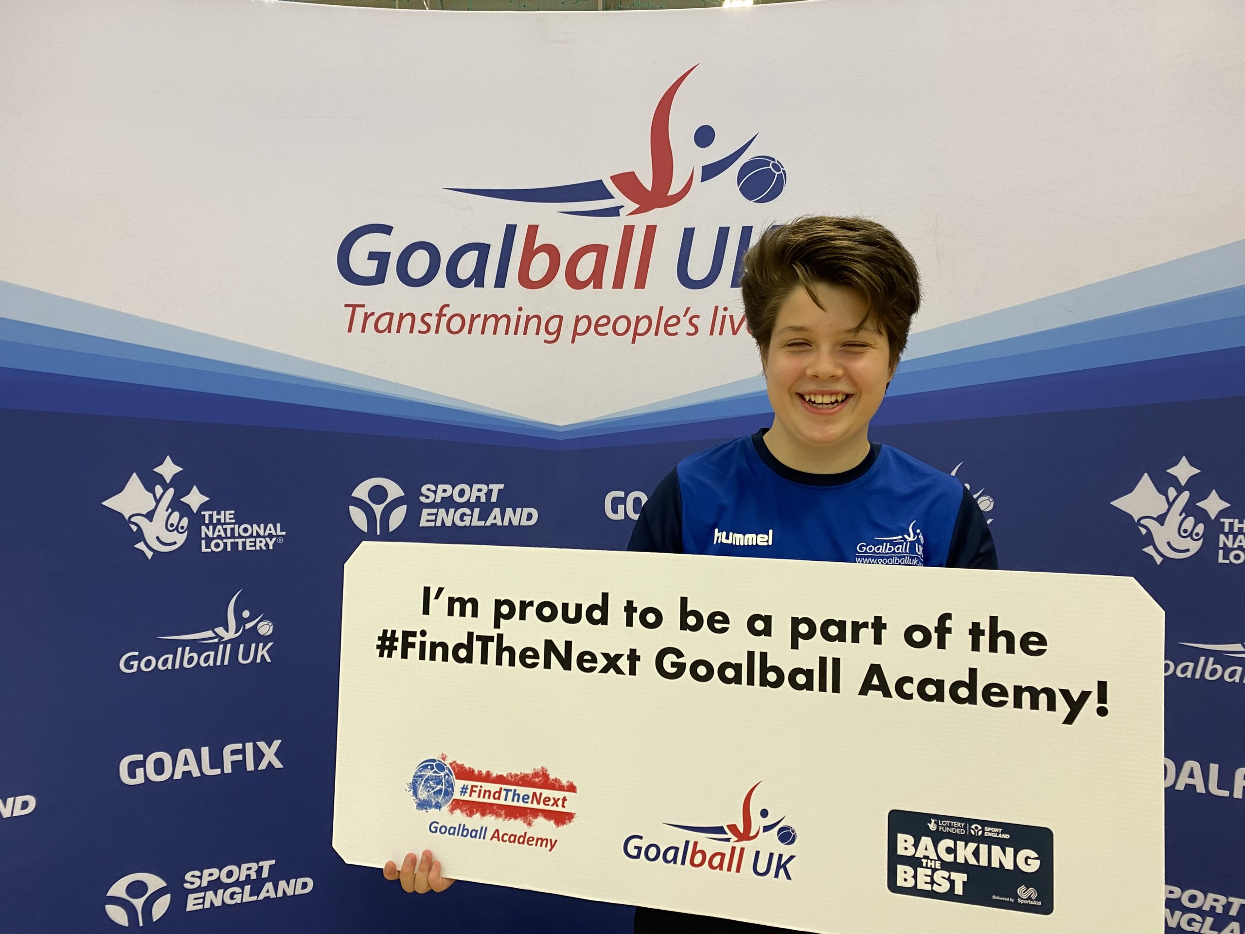"""Freya Gavin stood holding a sign which reads """"I'm proud to be a part of the #FindTheNext Goalball Academy"""" with a big smile whilst laughing!"""