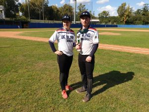 Freya Gavin stood with a team mate for UK Blind Baseball at a tournament. They are in their jerseys and stood next to a baseball pitch.
