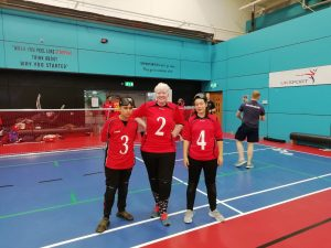 Freya Gavin stood in the Lancashire Lion's novice team photo in front of a goalball goal in their jersey's.
