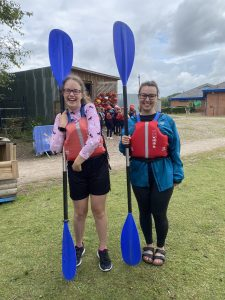Keira Mills and Natalie Herbert of the Goalball Academy team holding canoe paddles up facing the sky with big smiles at a water sports centre.