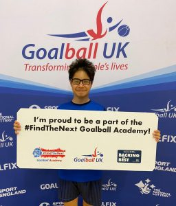 Max Dyble standing in front of a Goalball UK banner holding a board which reads
