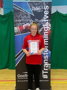 Ruby Hudson stood in front of a Goalball UK banner holding her referees course completion certificate after the 2021 Summer Camp.