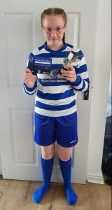 Ruby Hudson standing in front of a white door in her football kit holding a mini trophy, well done Ruby!