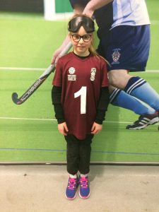 Ruby Hudson standing in front of a wall at York St John University in a Scarborough goalball kit.