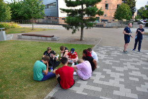 Summer Camp 2021 group all sat together in a circle on a patch of grass thinking of answers in the joint camp quiz.