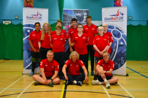 Summer Camp 2021 group photo. All wearing red summer camp shirts in front of Goalball UK banners.
