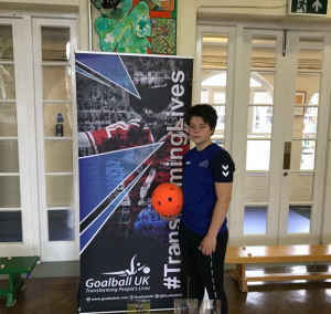 Freya Gavin holding an orange goalball next to a Goalball UK promotional banner in a school hall.