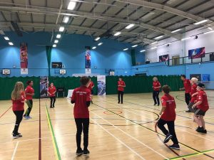 Summer Camp 2021 team in a circle in a sports hall warming up. All are wearing their summer camp t-shirts.