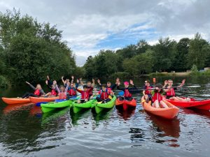 Team picture of the #FindTheNext Goalball Academy team on the water in canoes. All are holding their hands in the air and have big cheesy smiles!