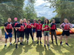 The team stood together at the National Water Sports Centre wearing life jackets and smiling before going into canoes!