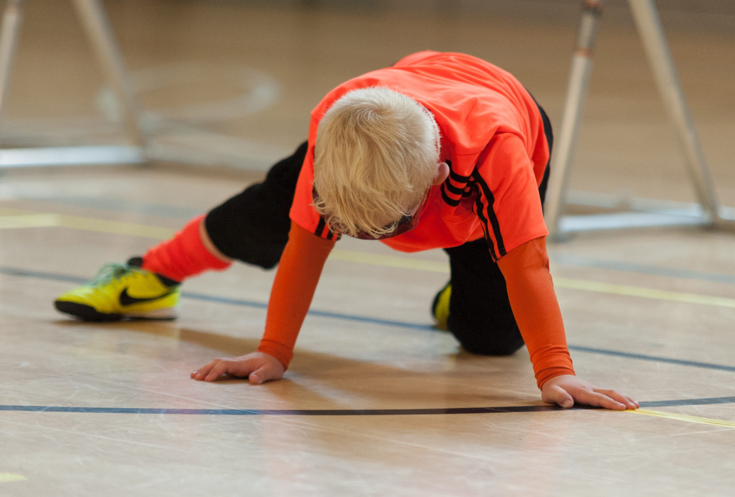 A young player in an orange shirt finding their way back to their position on their hands and knees on court.