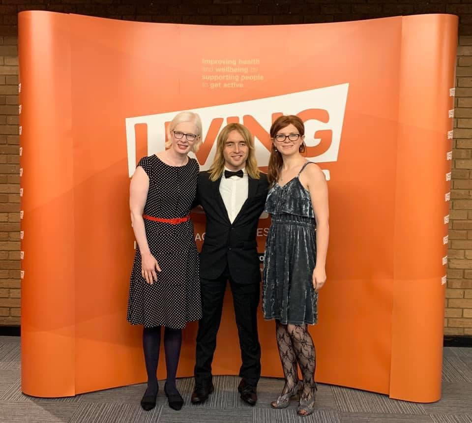 Sarah Leiter, Warren Wilson and Emily Watton stood together in formal attire in front of an orange background at an awards ceremony.