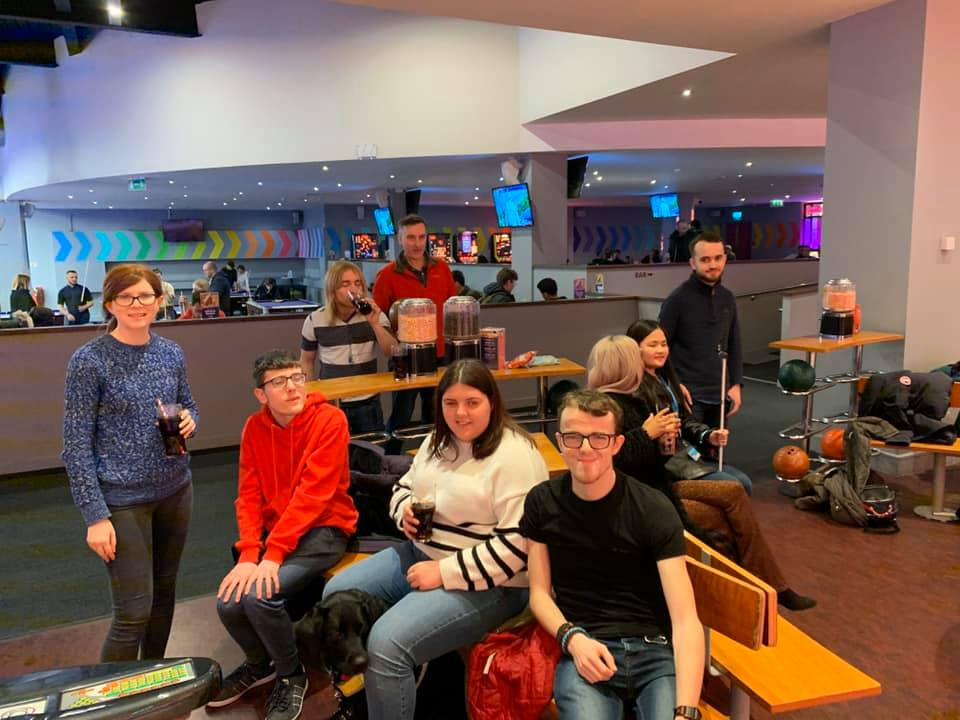 A group of Cambridge Dons players sat on chairs and booths at a bowling alley.