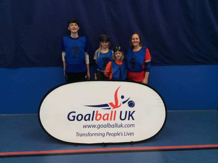 South Wales group photo wearing blue vests over playing tops behind a Goalbll UK banner.