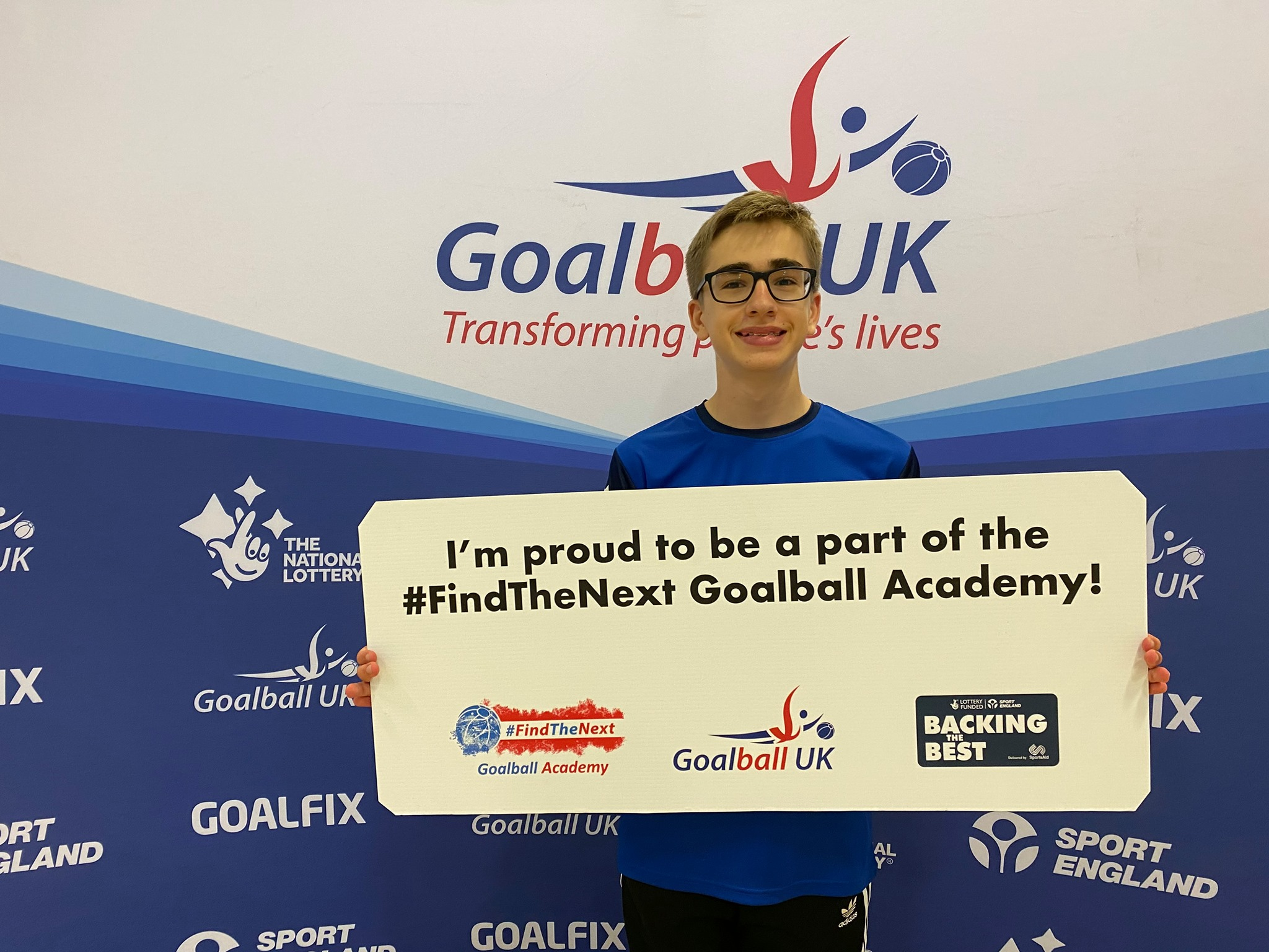 Harry Bainbridge in his Goalball Academy shirt holding up a sign which reads