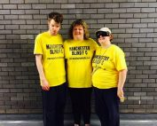Helen Lawson stood on the right along with two friends in yellow t-shirts in front of a grey brick wall.