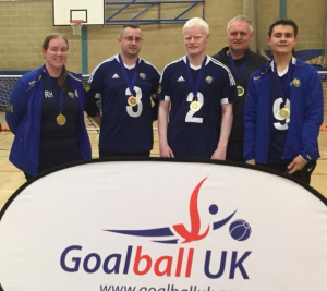 4 Winchester goalballers and a coach stood behind a Goalball UK banner