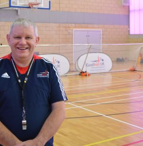Robert Avery stood in a Goalball UK referee's top in front of a goalball goal.