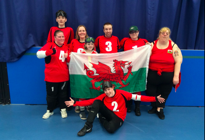 South Wales group photo with 7 people in red South Wales tops stood at the back all holding a Wales flag with one player holding his arms out with a smile crouched in front.