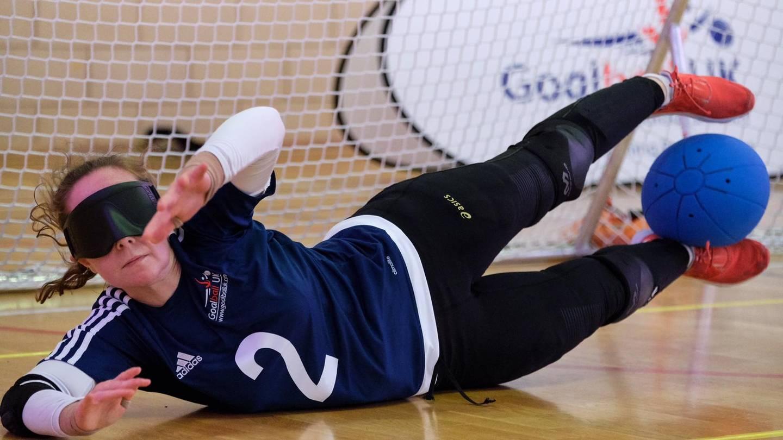 Antonia Bunyan in a GB shirt saving a goalball shot with her legs.