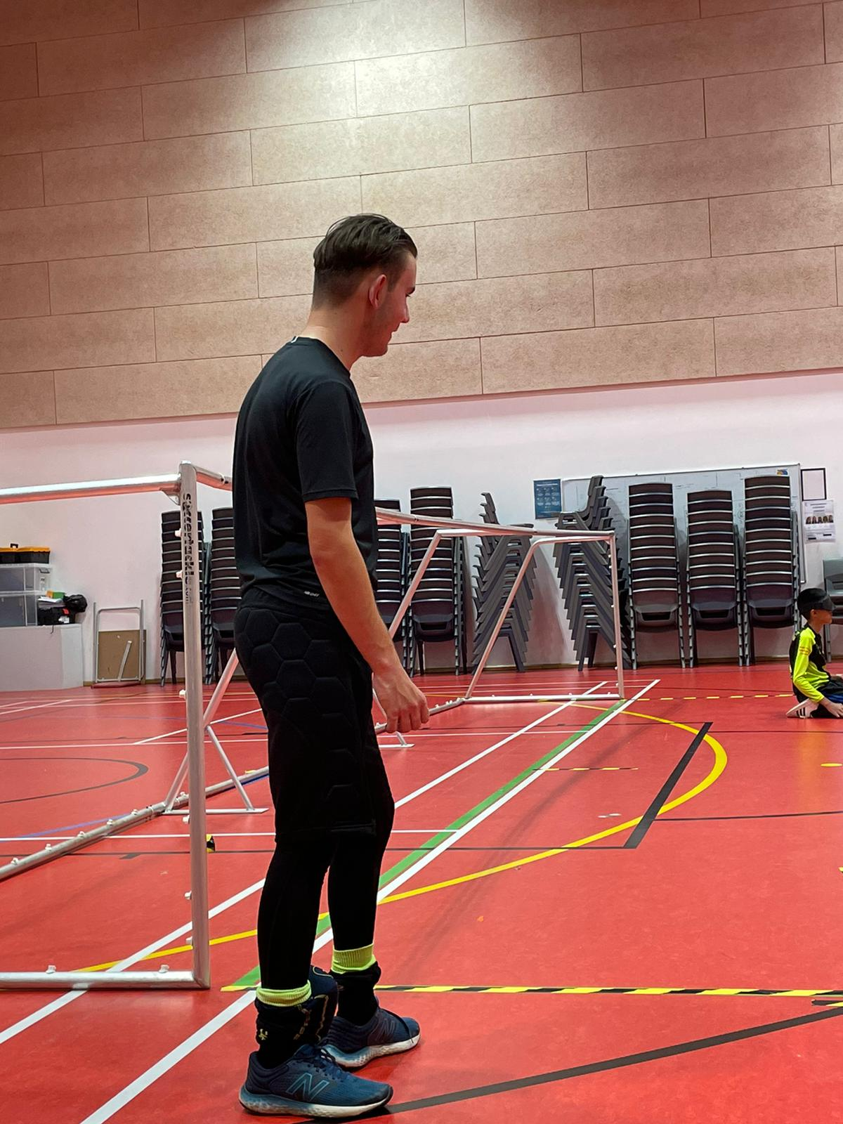 Jacob Hare stood next to the right corner of a goalball goal in a sports hall in a training session.