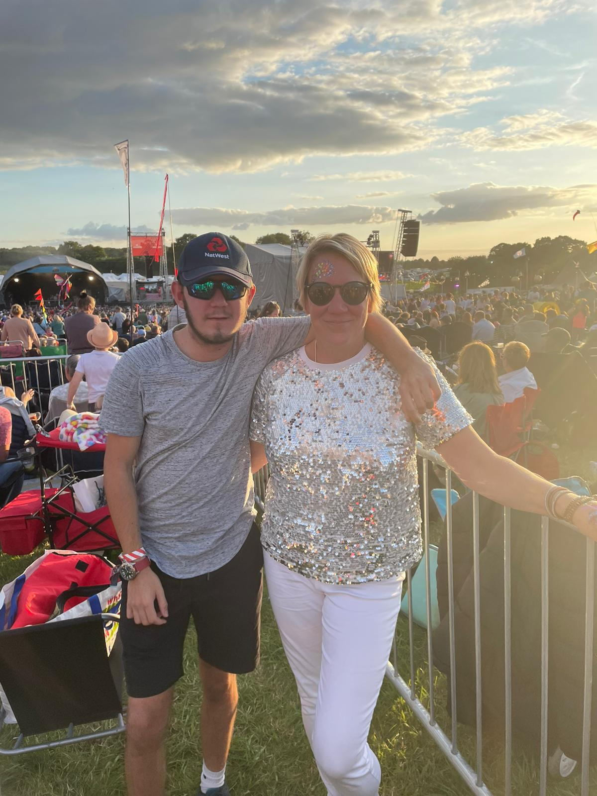 Jacob stood with his mum Louise Potter at a festival. There are lots of people behind them on a blue but partially cloudy day with the sun setting in the background.