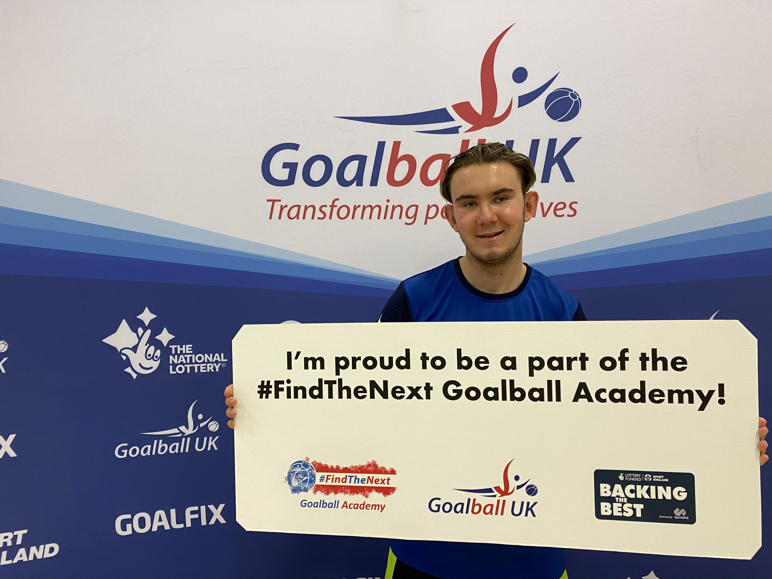 Jacob Hare stood in front of a Goalball UK banner with a sign saying