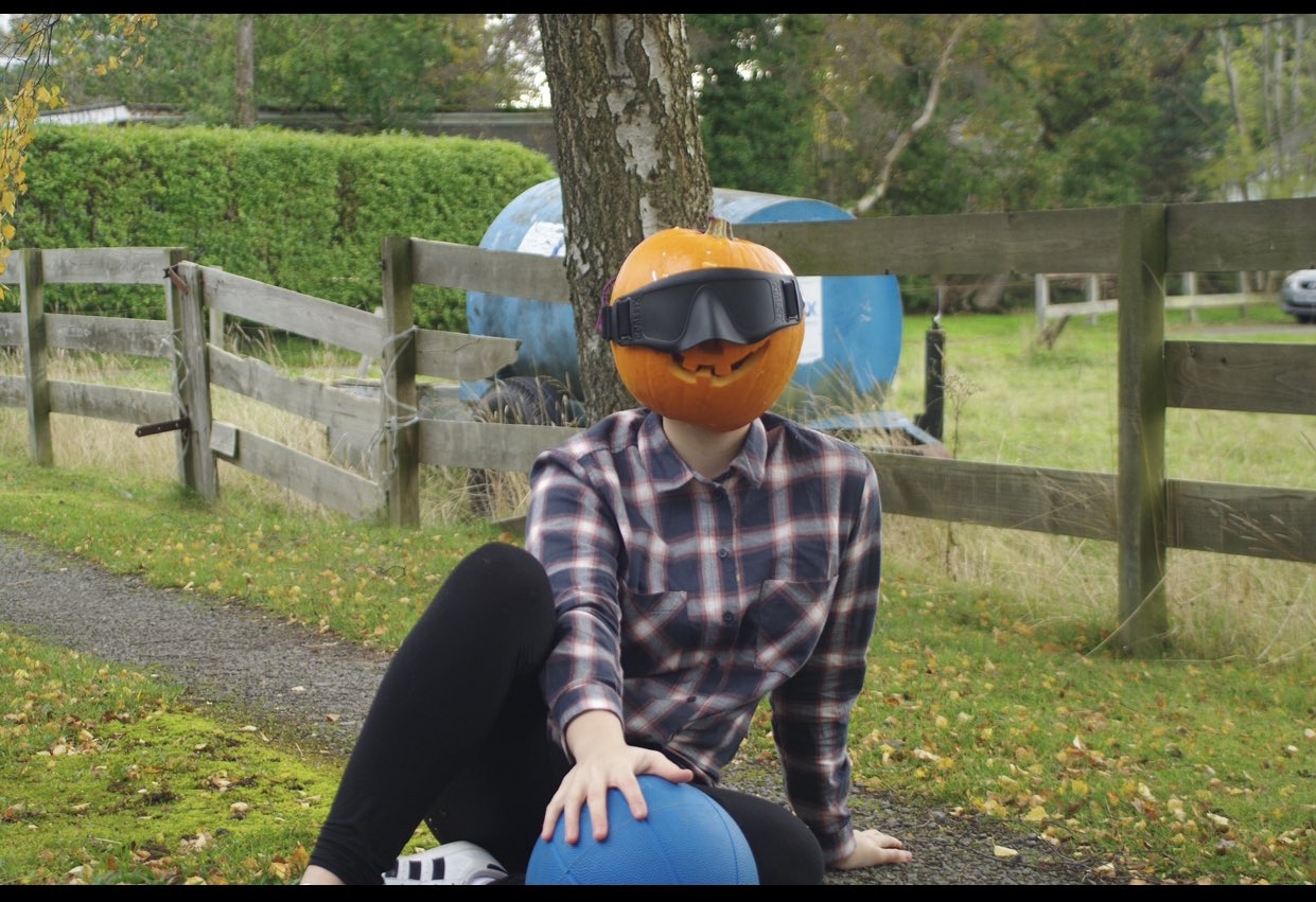Samantha Gough wearing a chequered shirt laying in a goalball defensive position with a pumpkin on her head!