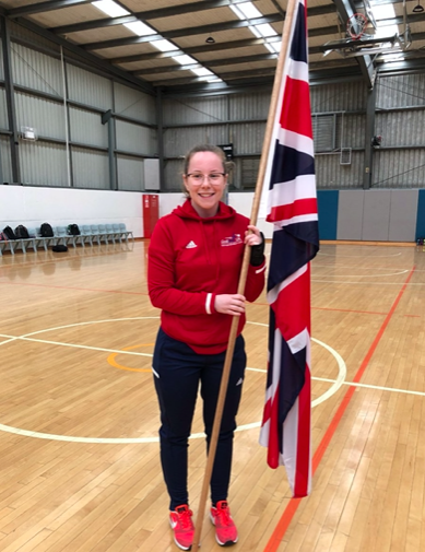 Antonia Bunyan at the U19 World Championships in Australia holding the GB flag in a GB tracksuit.