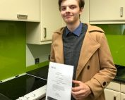 Tom Lancaster stood in a kitchen holding a certificate whilst wearing a beige coat.